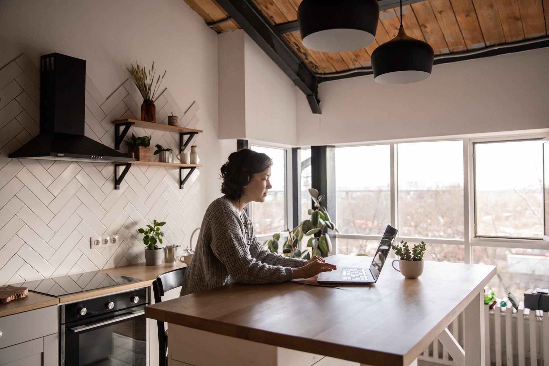 kuchyna-s-ostrovcekom-velky-oknom-ciernym-digestorom-zena-pracuje-v-kuchyni-s-notebookom