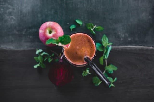 smoothie-v-pohari-so-slamkou-bylinky-jablko-polozene-na-ciernom-stole