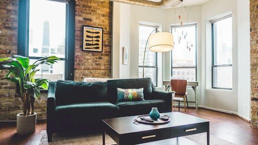 styl-do-interieru-inspirovany-skandinaviou-smaragdova-pohovka-drevena-podlaha-velke-okna-tehlova-tapeta-velky-kvet