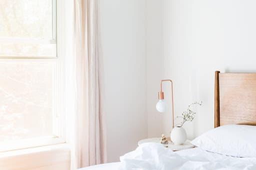 minimalisticky-styl-do-interieru-v-spalni-biele-obliecky-mosadzna-lampa-okno-s-kremovym-zavesom