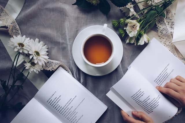 biela salka caju na stole okolo biele kvety a dve otvorene knihy