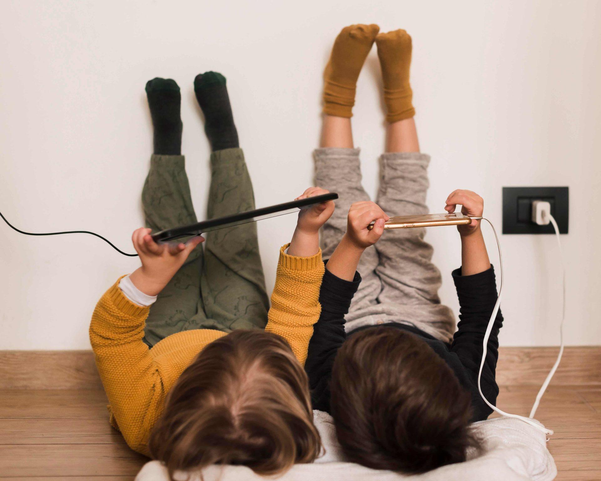 deti leziace na zemi s tabletmi zapojenymi v zastrcke