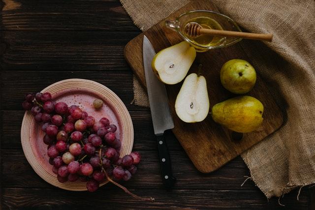 rozkrajane hrusky a hrozno na tanieri s medom